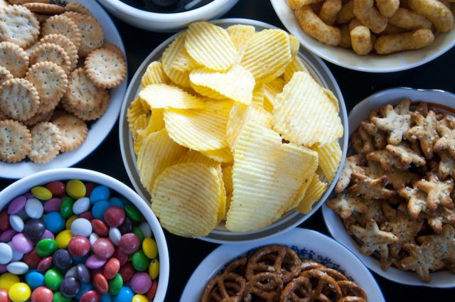 Snacks, chips and candies laid out on a table.