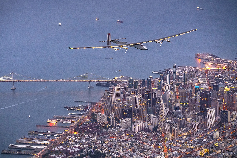 A solar-powered plane flies over San Francisco