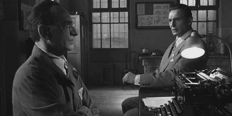 Liam Neeson as Schindler sitting down at a desk looking at a man.