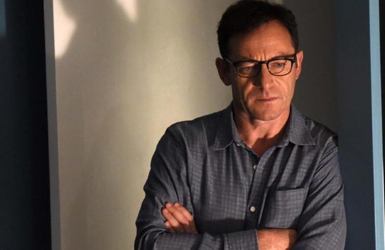 Jason Isaacs wearing glasses with his arms folded, leaning against a wall and looking down