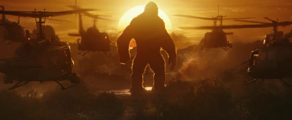 Kong stands in the sunset as helicopters approach