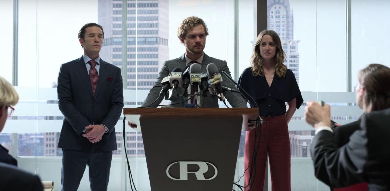 Tom Pelphrey, Finn Jones and Jessica Stroup standing behind a podium in the middle of a press conference in Iron Fist