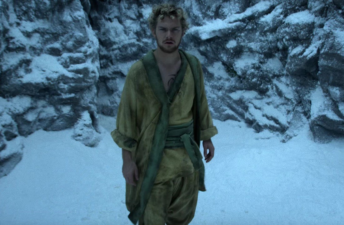 Finn Jones, wearing a yellow robe, and walking through the snow looking dazed