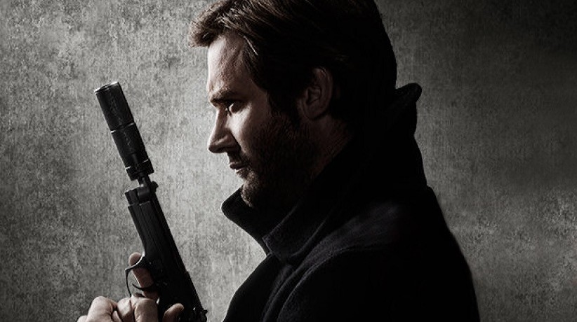 A man holding a gun up to his face in a promo shot for NBC's Taken prequel series