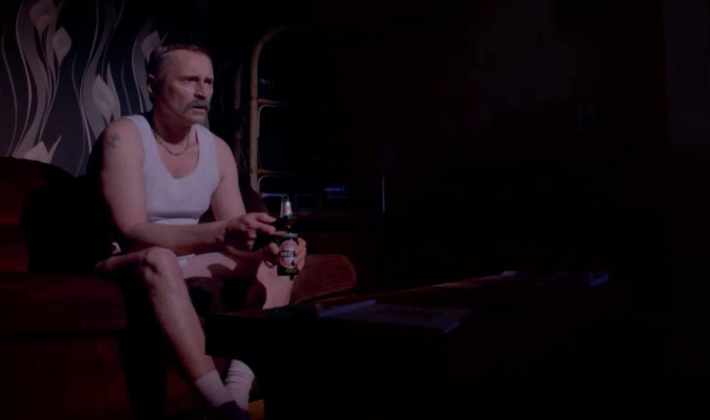 Robert Carlyle sitting with a beer in T2: Trainspotting