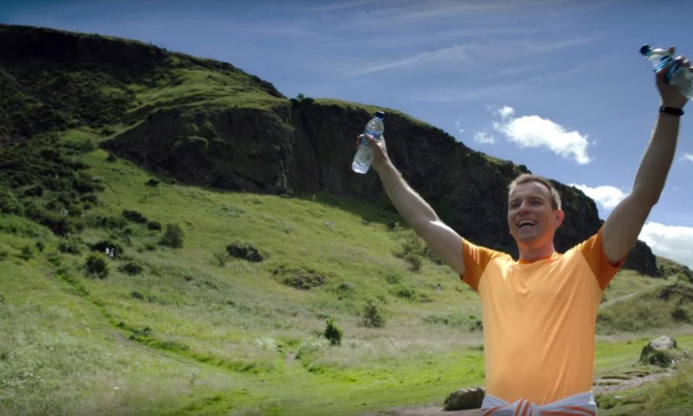 Ewan McGregor with his arms up, and water bottles in either hand, while smiling