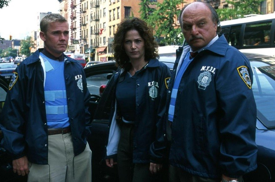 The cast of NYPD stands in front of a cop car, looking off to the left