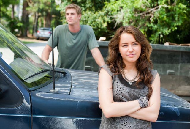 Miley Cyrus with her arms folded in front of a car, with Liam Hemsworth in the background