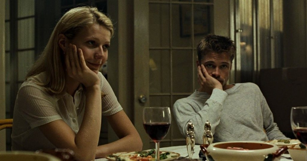 Gwyneth Paltrow and Brad Pitt at a kitchen table, both with their heads in one hand respectively