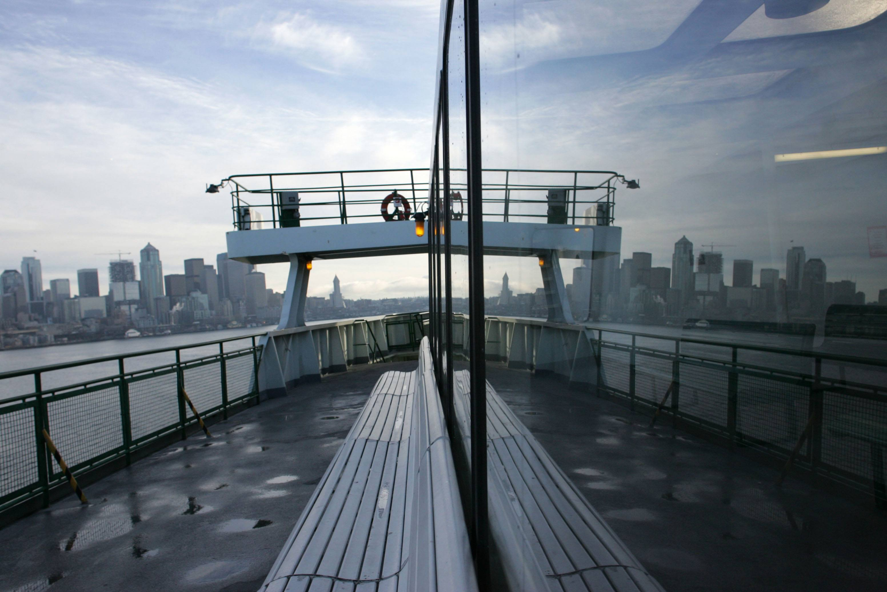 The Seattle skyline is reflected in the window of a Washington State Ferry