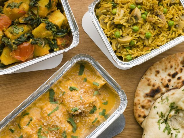 Above View Of Selection Indian Take Away Dishes In Foil Containers On Wooden Table.