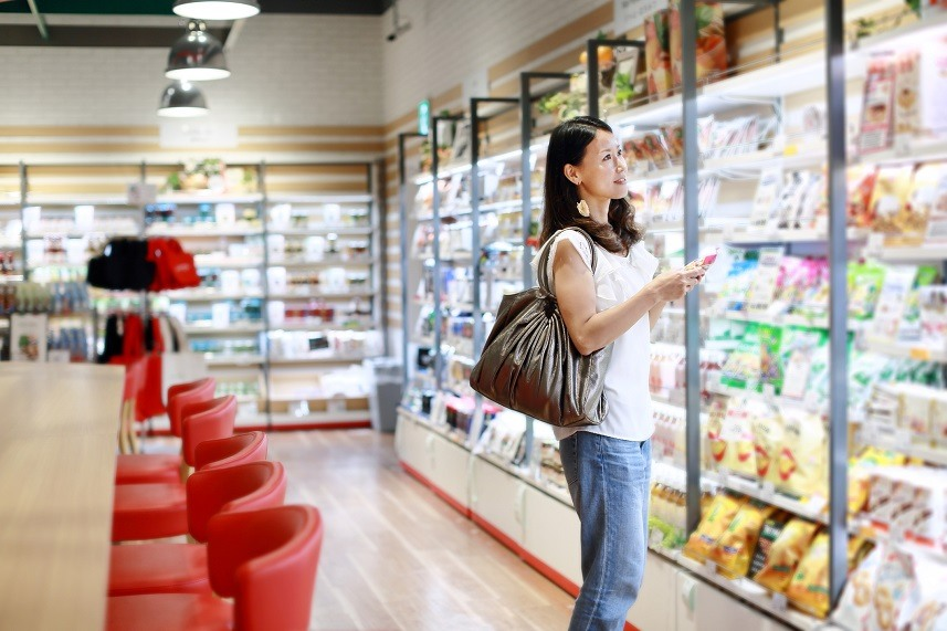 woman with cell phone doing shopping