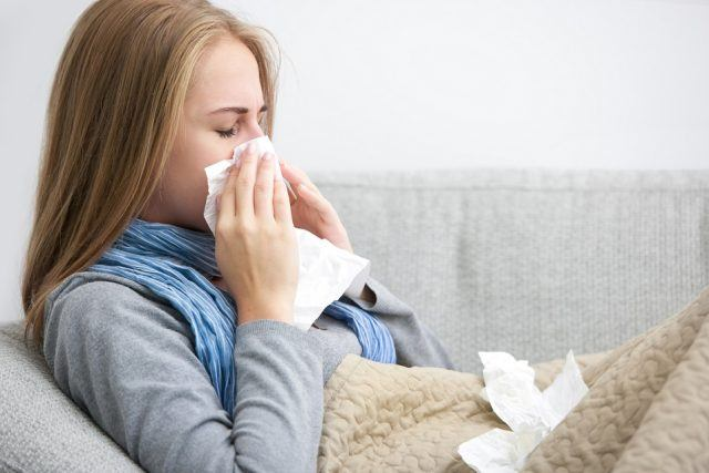 Woman sneezing into a tissue while sitting on a couch.