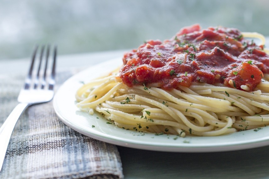 Spaghetti and home made tomato sauce on green plate.