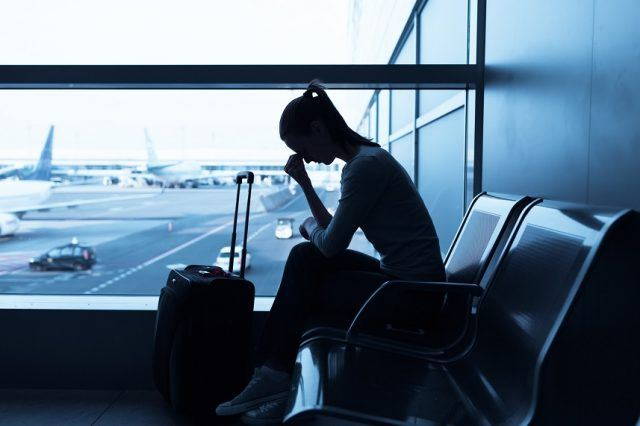 Stressed woman in an airport waiting for an overbooked flight