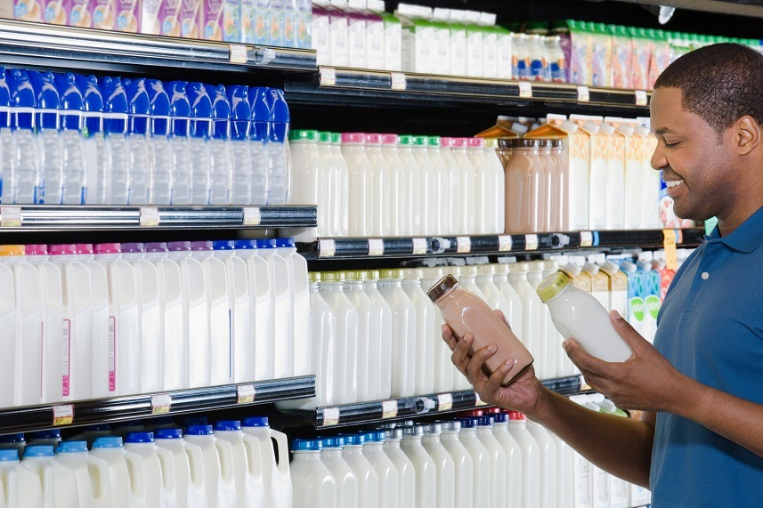 Young man in supermarket choosing milk