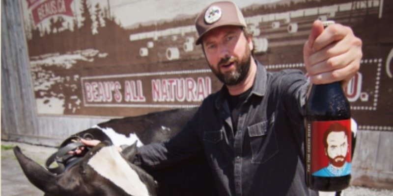 Tom Green holding up a bottle of The Tom Green Beer next to a cow