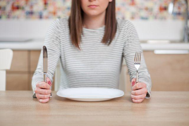 hungry woman with nothing on her plate