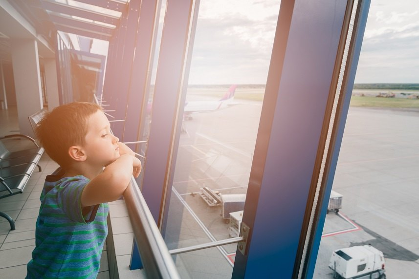 child at the airport, traveling and waiting near window