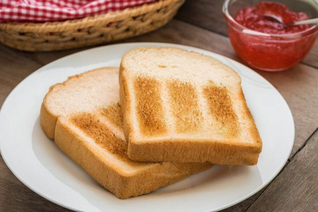 Two pieces of toast on a plate and strawberry jam in a bowl to the side.