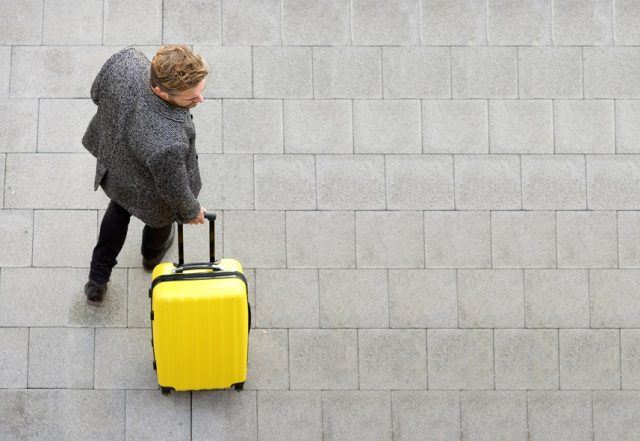 man walking with suitcase traveling abroad