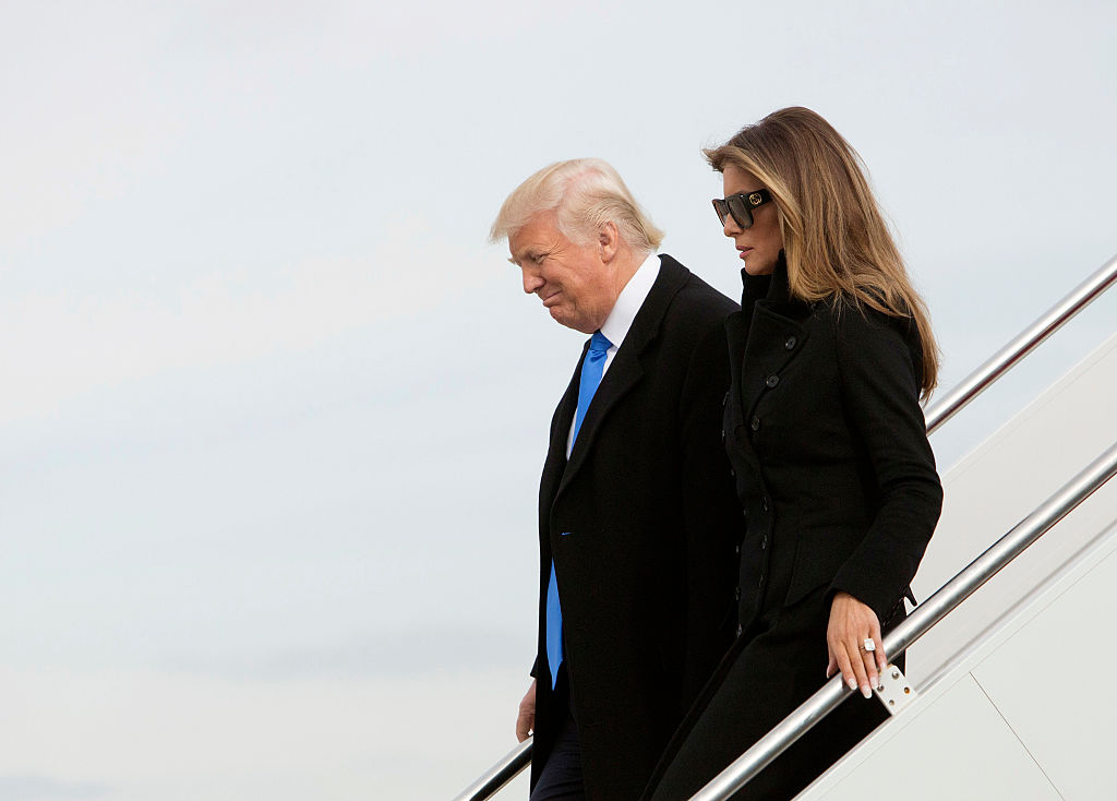 Donald and Melania Trump exit an airplane.