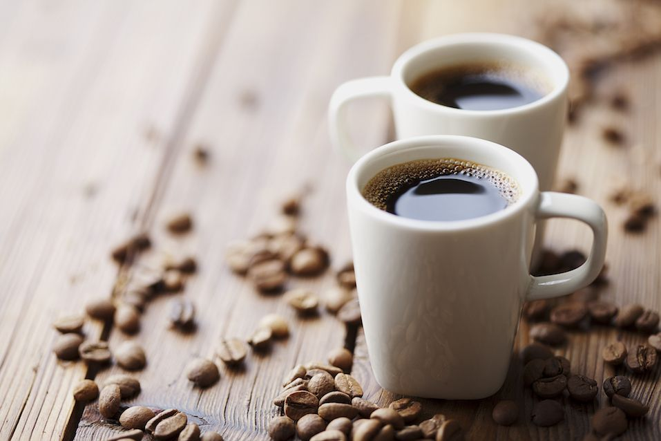 Cups of expresso surrounded by coffee beans