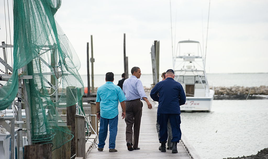 President Barack Obama walks near fishing boats.