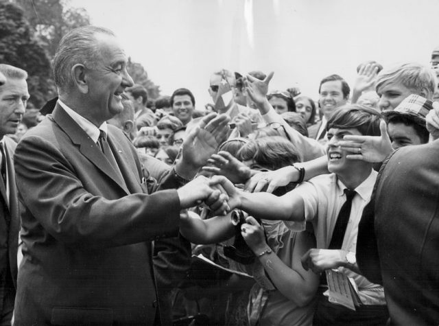 US President Lyndon B Johnson shaking the hands of crowds of people.