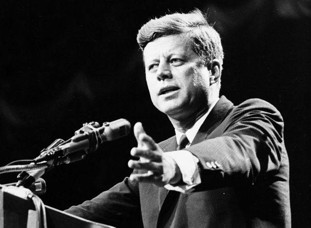 John F Kennedy in front of a microphone.