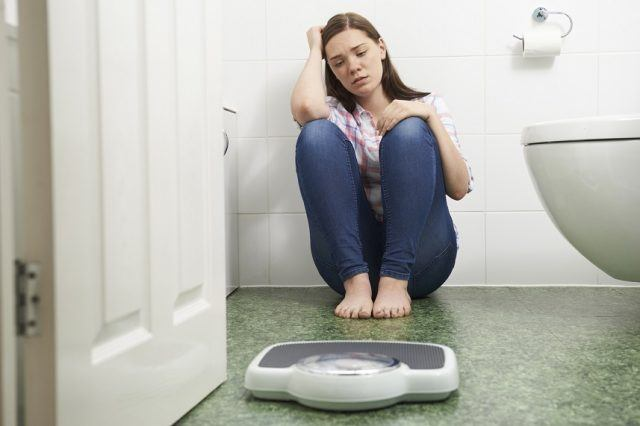 Woman looking stressfully at a scale.