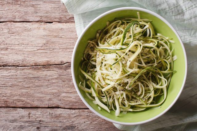 Raw zucchini pasta in a bowl close up on the table. horizontal top view.