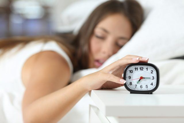Asleep girl stopping alarm clock