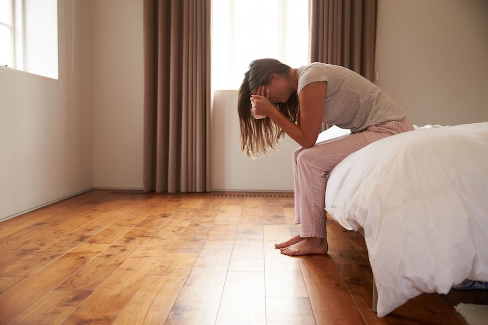 Woman Suffering From Depression Sitting On Bed And Crying