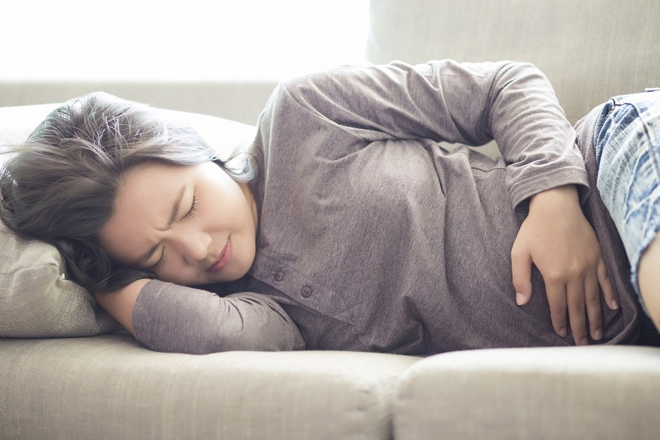 Woman lying on couch with hand on stomach suffering from a stomachache.