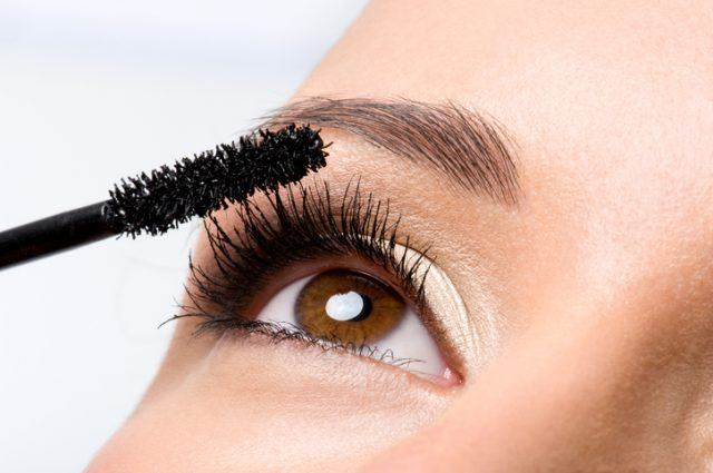 Woman applying mascara on her eyelashes