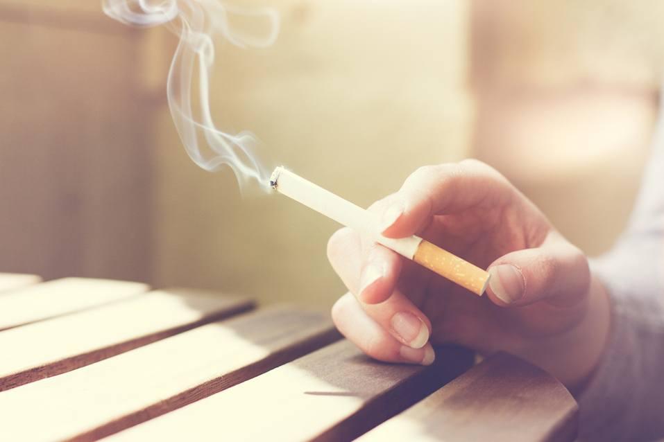 Person holding a lit cigarette