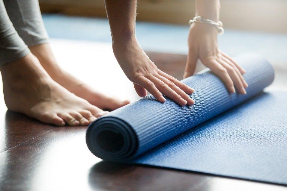 Young woman folding blue yoga mat