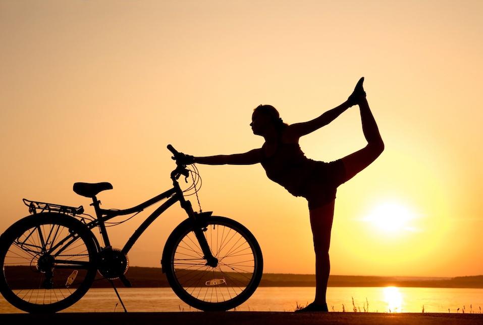 woman doing yoga next to her bike