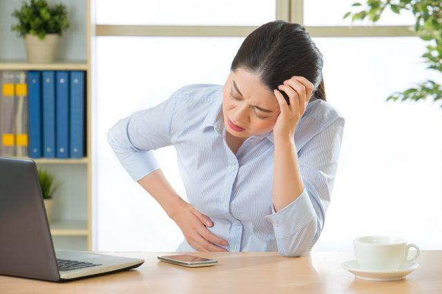 A woman holding her stomach while sitting in an office.