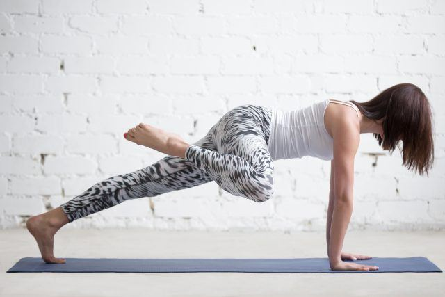 woman practicing yoga on her yoga mat