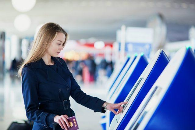 woman in airport doing self check-in