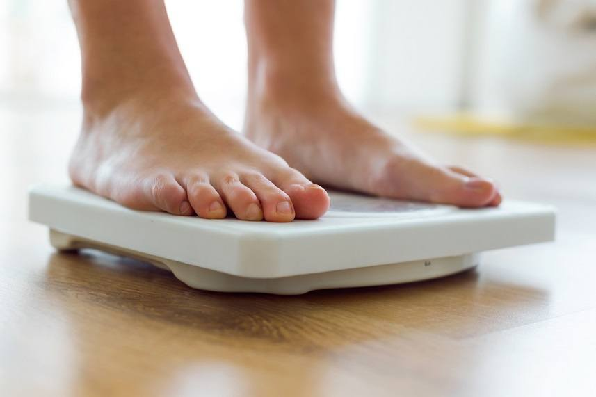 young healthy girl on home scales