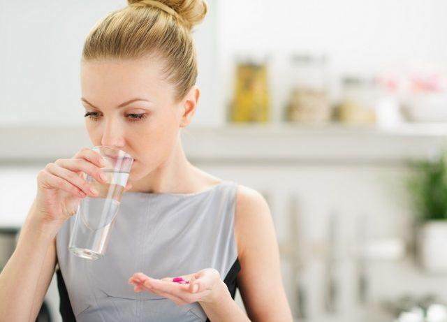 A woman drinks a glass of water with her pills.