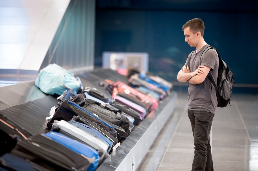 passenger waiting at conveyor belt to pick his luggage