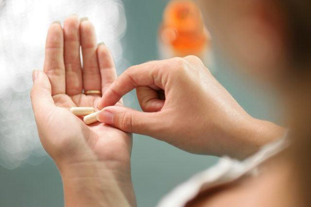Close up view of young woman holding ginseng vitamins and minerals pills in hand with capsule bottle on table. High angle view.