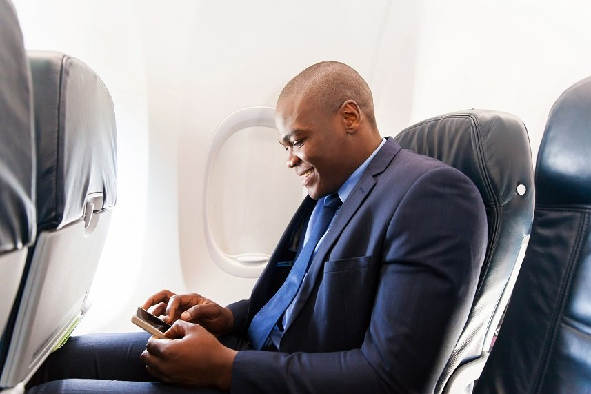 african airplane passenger using smart phone