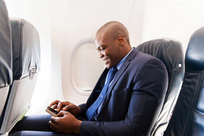 african airplane passenger using smart phone