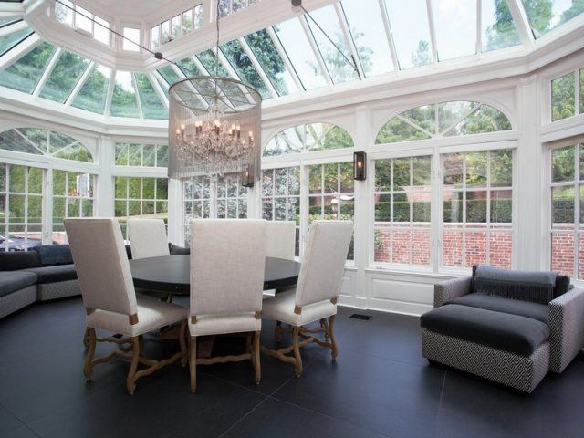 The living room of Alicia Keys' mansion shows floor to ceiling windows, a vaulted ceiling and a modern chandelier.