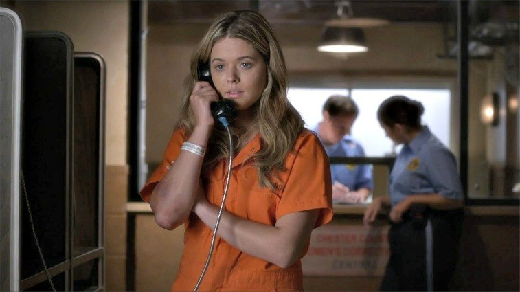 Alison DiLaurentis on Pretty Little Liars blonde girl in orange prison jumpsuit on payphone with officers behind her